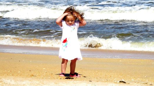 Our pretty little niece loving the wind and the beach!